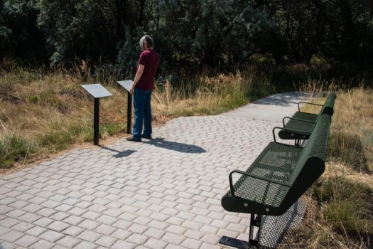 A trail user reads one of the Braille signs along the Braille Trail in Beck Lake Park in Cody, Wyoming The signage along the 1/4-mile trail discusses the natural features of the area in both printed English and Braille. The location of the signs is made evident to those walking the trail through the use of bricks that change the tactile surface, indicating to a blind user that there is a sign to be read.