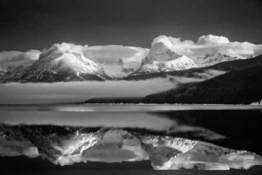 Snow-covered peaks reflect in Lake McDonald on a winter day. The 10-mile long lake is the largest in Glacier National Park in Montana.