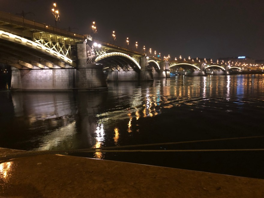well lit bridge over pitch black waters in budapdest