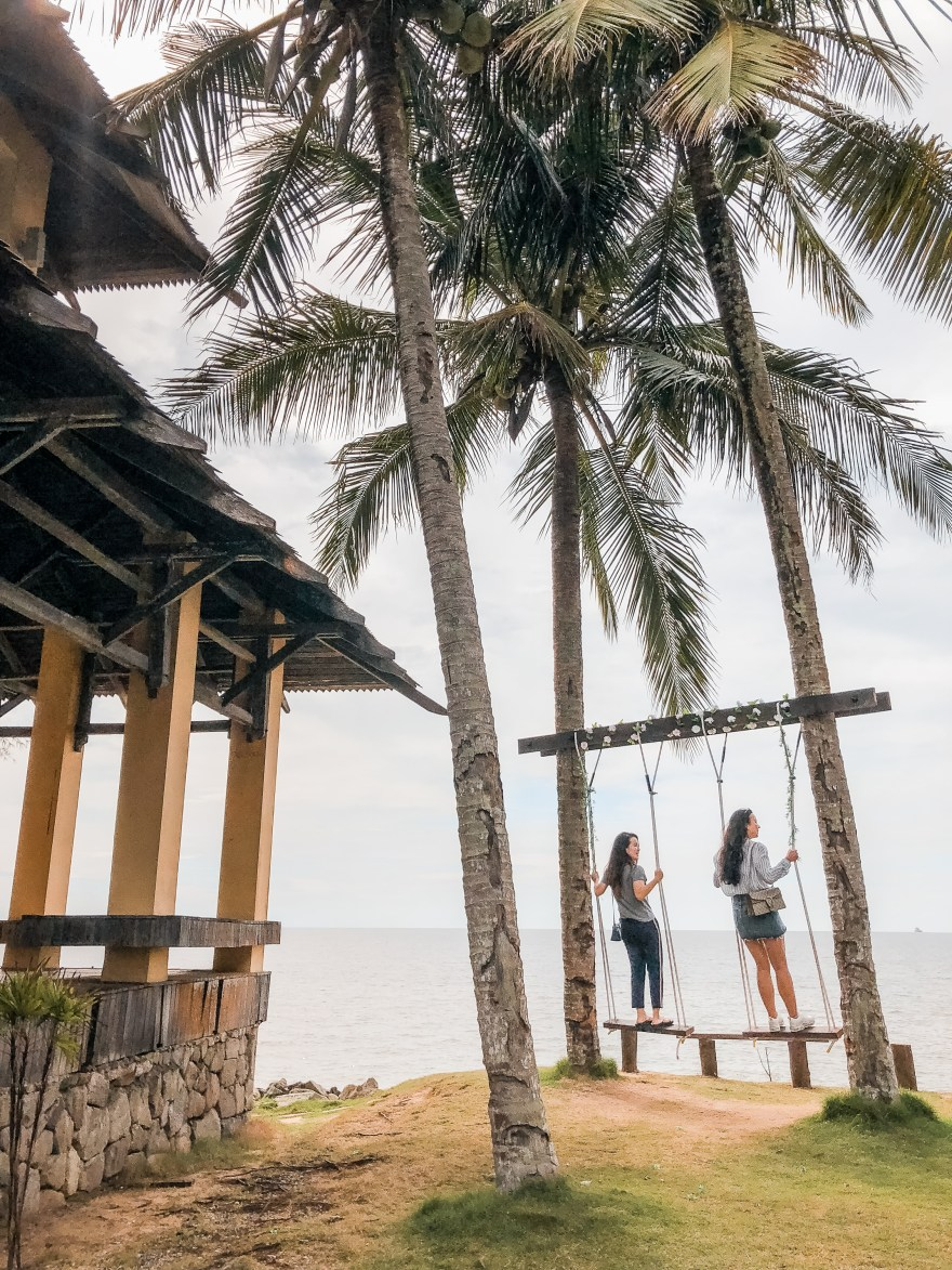 girls on swing in front of palm trees near water borneo