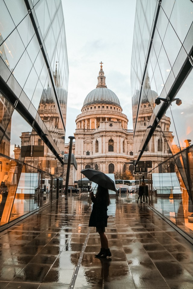 girl standing in front of st pauls cathedral on a rainy day