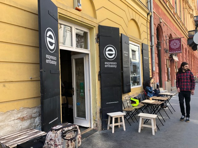"man with long hair and strippy short walking past coffee shop in budapest that has a yellow facade and black doors which say ""espresso embassy"""