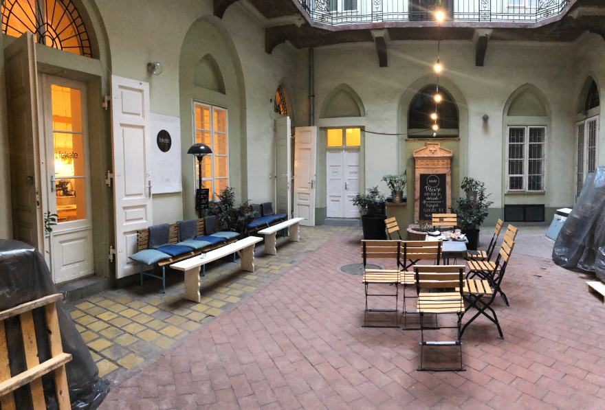 courtyard with red yellow bricked floors green walls wooden chairs and white benches