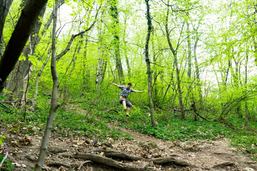 man leaping in the air of the ground of a muddy path in a lush green forest