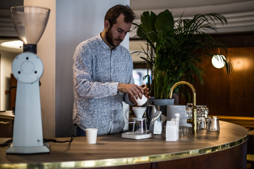 man with beard and hair and a paisley shirt preparing a cappucino in v60 presser