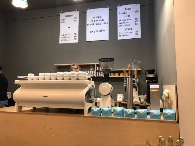 counter at coffee shop in budapest that has a white coffee machine with blue bags of roasted coffee beans