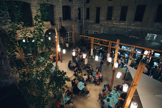 people sat in outdoor courtyard of ruin bar in Budapest