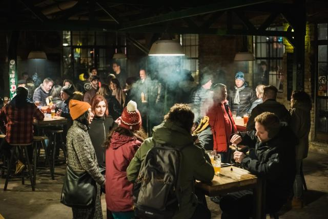 group of people drinking beer at a ruin bar in Budapest