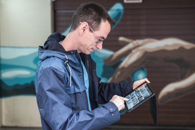 Man glasses ipad handds touching wall garage