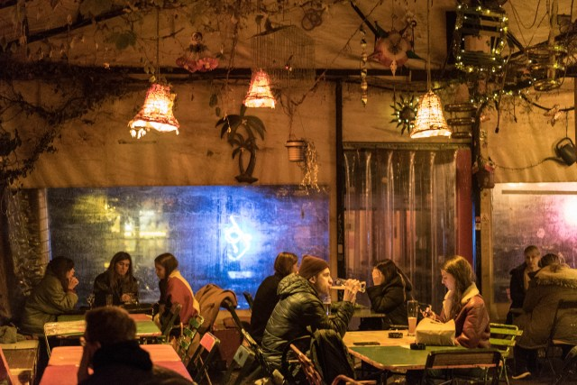people sat on tables in budapest's 7th district bar