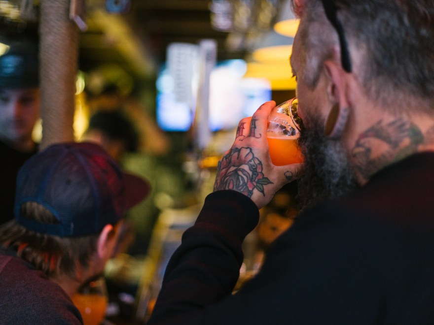 tattooed-man-drinking-beer-in-budapest-bar