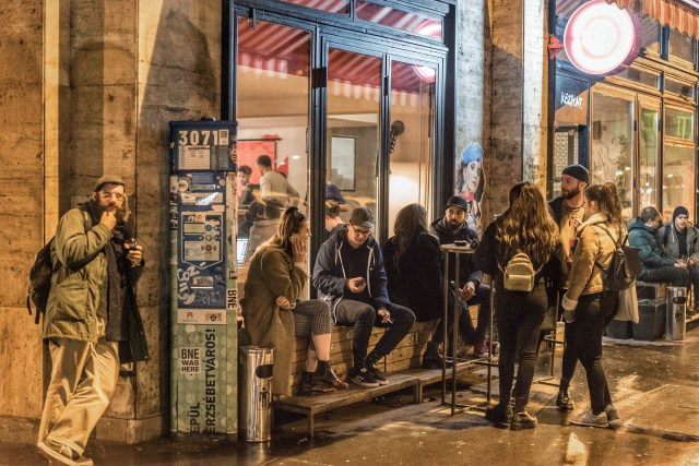 people smoking in front of bar in budapest's 7th district
