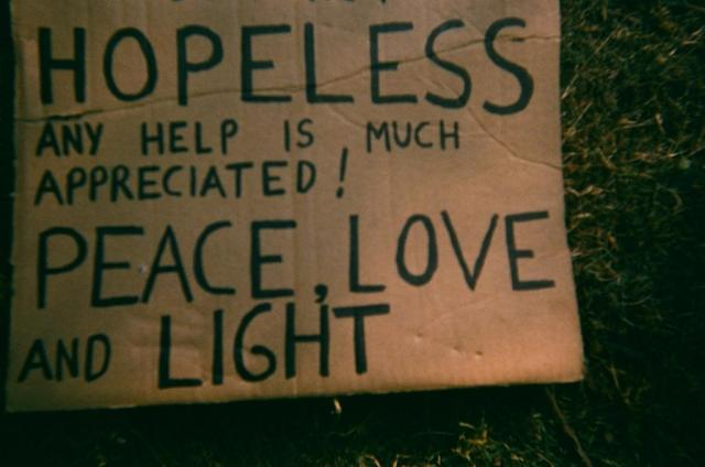 "cardboard sign on grass that reads ""hopeless any help us much appreciated. Peace love and light"""