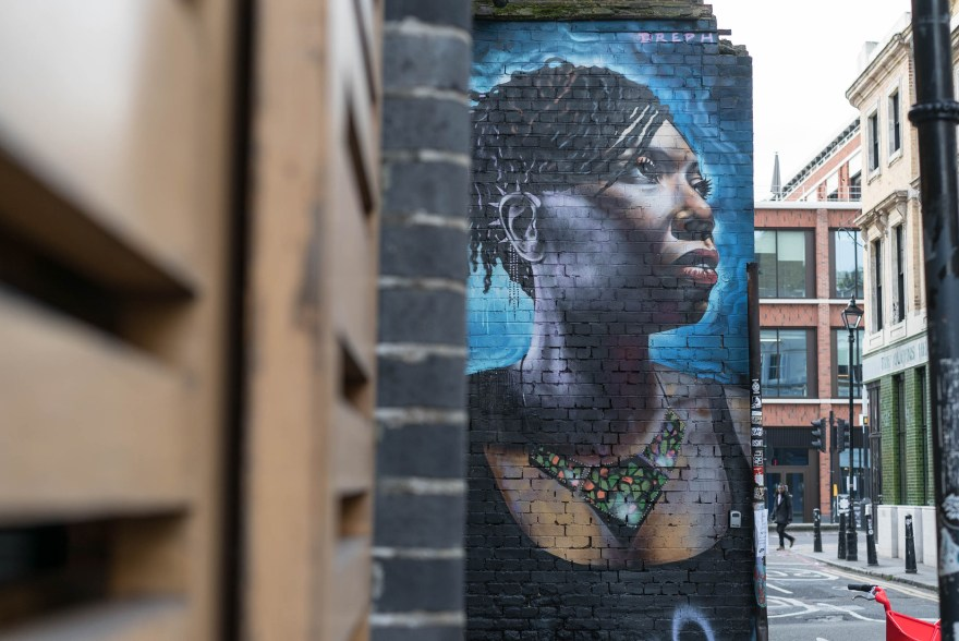 street art in brick lane showing a black women with dreadlocks wearing a green and red necklace