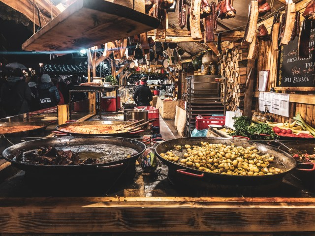 wooden cabin kitchen with hanging meats and big pots filled with potatoes and meat at Vörösmarty Square Christmas market