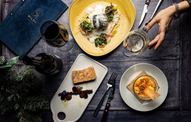 """black table with filled with plates of food a bottle and glass of red wine and a glass of white wine which a women hand is reaching and a blue menu thats says """"hilda' on it"""