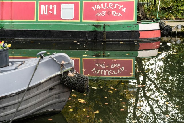 Green Red Yellow Narrowboat on murky water which