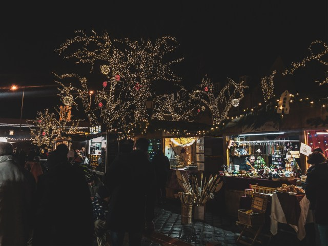 trees beautifully decorated with failry lights in front of wooden stalls selling christmas themed products