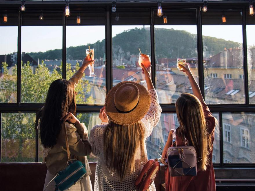 three girls stood with cocktails in their hands raising a toast whilst looking out of a window with a view of gellert hill budapest