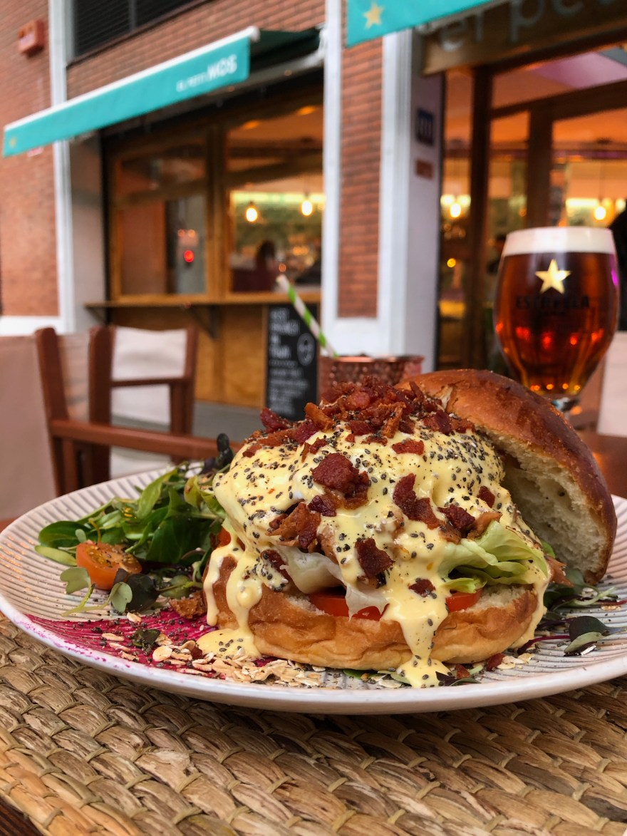 white plate with eggs overflowing eggs benedict inside a brioche bun and a beer with a gold star on the glass