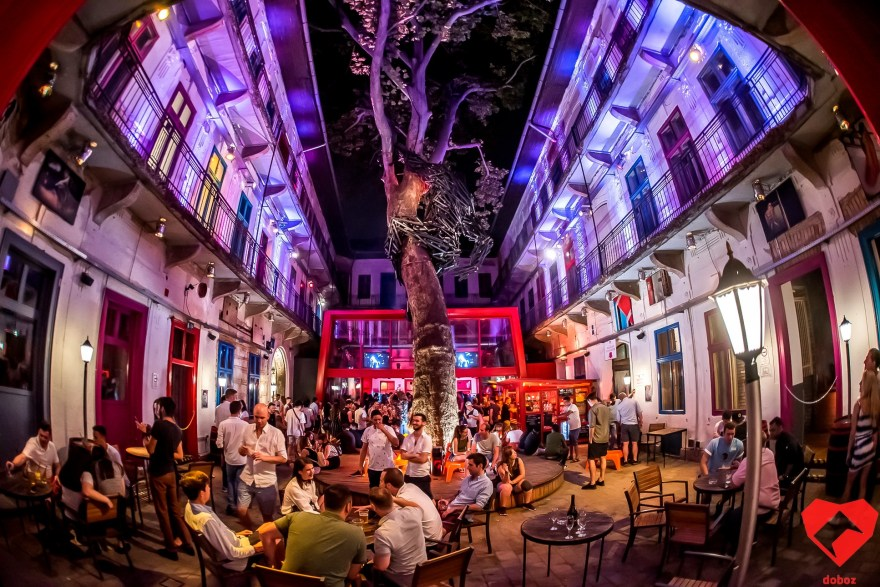 neon lit courtyard filled with people sat on tables with a huge tree in the middle