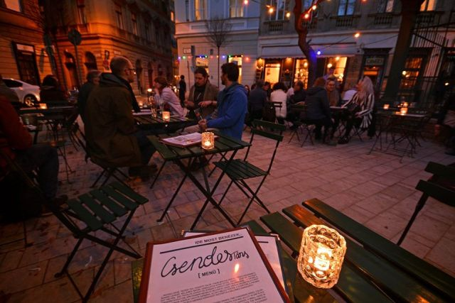 Csendes Társ budapest outdoor bar at nigh with people enjoying food and drink on candlelit tables