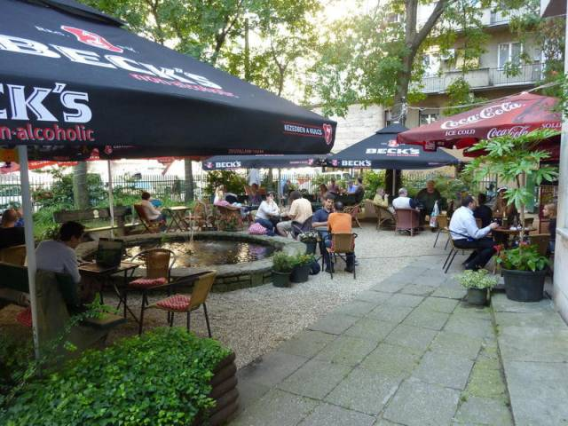 Figaro Garden Budapest outdoor bar terrace with people enjoying some food and drink on tables surrounding a pond in the centre