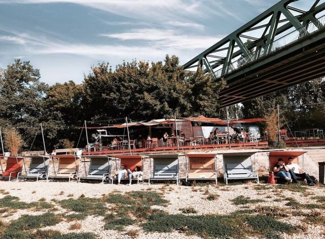 kabin budapest outdoor bar with colourful wooden cabins seating on sand