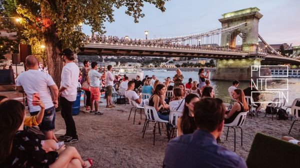 pontoon budapest outdoor bar next to danube river under the chain bridge packed full of people drinking and chatting