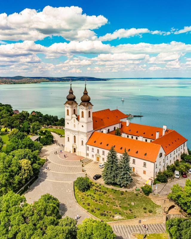 white church in tihany with orange tiled roof surrounded by greenery right next to a light blue lake balaton on a sunny summers