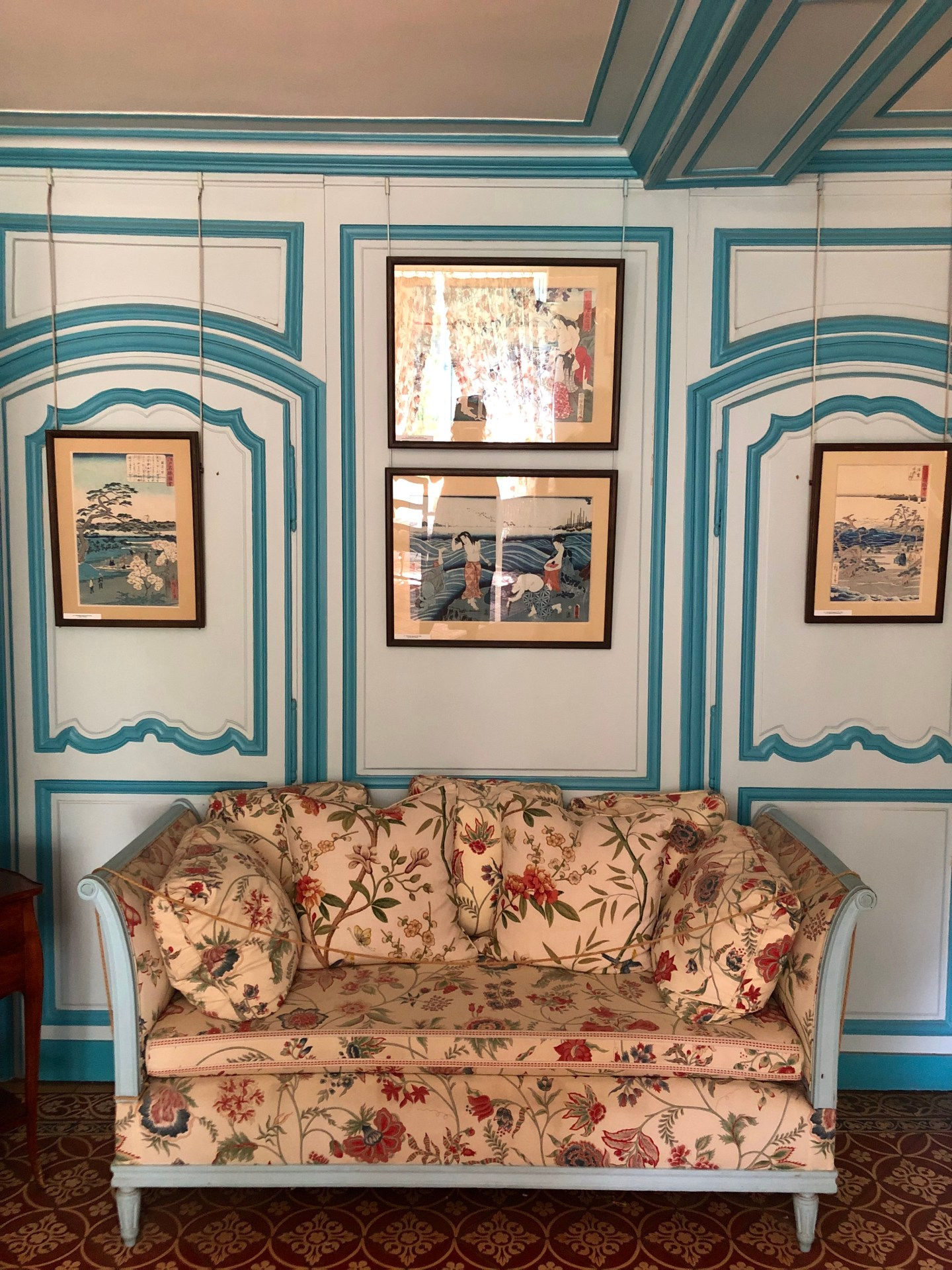 The blue sitting room of Claude Monet is adorned with his collection of Japanese Ukiyo-e wood block prints. The walls and furniture are two blends of pale blue and teal with an appealing contrast of pink floral.