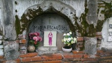 She may not have a marble grave marker but she has a photo and potted flowers.