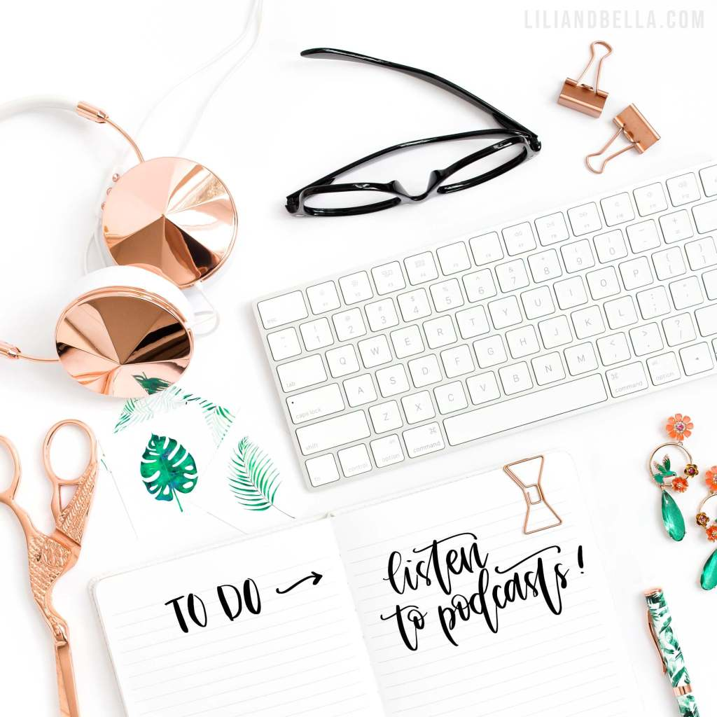 The top of a mompreneur's desk with a hand-lettered note to listen to podcasts