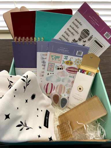 Archer & Olive March subscription box contents including stationery goods such as notebooks, stickers, stamps, and ink pads.
