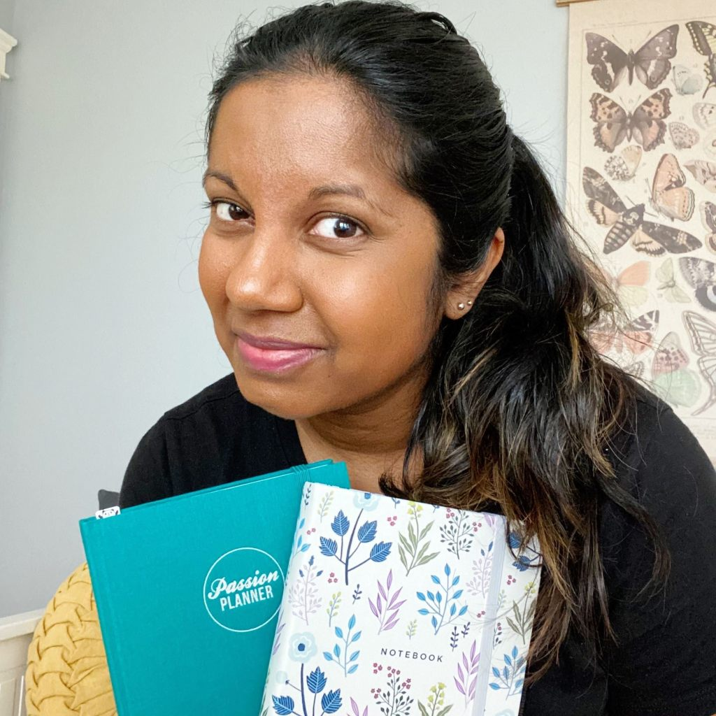A profile shot of Carola holding a teal Passion Planner and floral Archer & Olive notebook. and