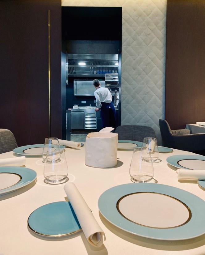 table dressée et vue sur la cuisine une étoile Michelin monlivault