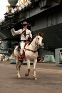 A man dressed as the Lone Ranger rides his horse along the pier as the aircraft carrier USS RANGER (CV-61) ties up behind him. The RANGER has returned to North Island following its deployment to the Persian Gulf region for Operation Desert Shield and Operation Desert Storm.