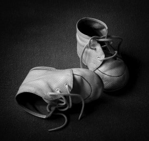 Pair of old tiny baby shoes. Black and white with copyspace.