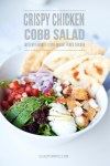 Bowl of cobb salad with pita and text overlay