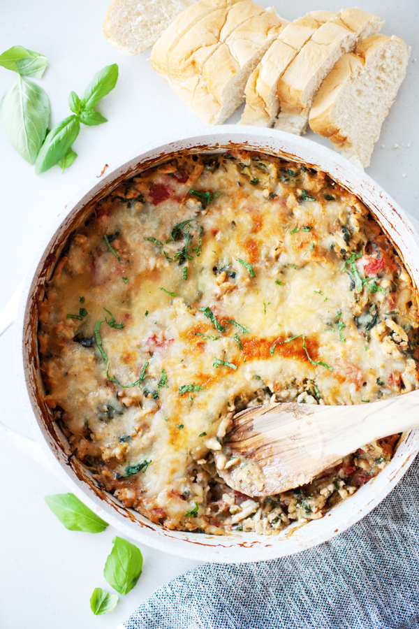 Cheesy spaghetti squash bake in one pan with a wooden spoon