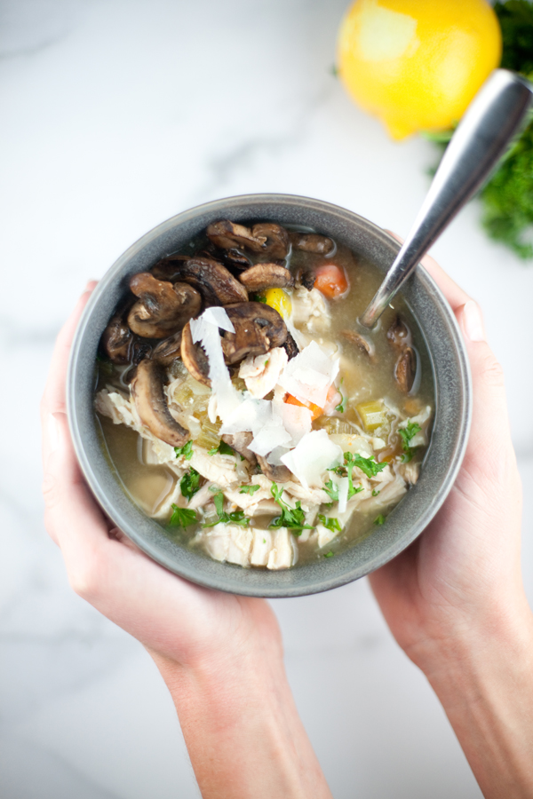 Bowl of lemony chicken soup with mushrooms on top