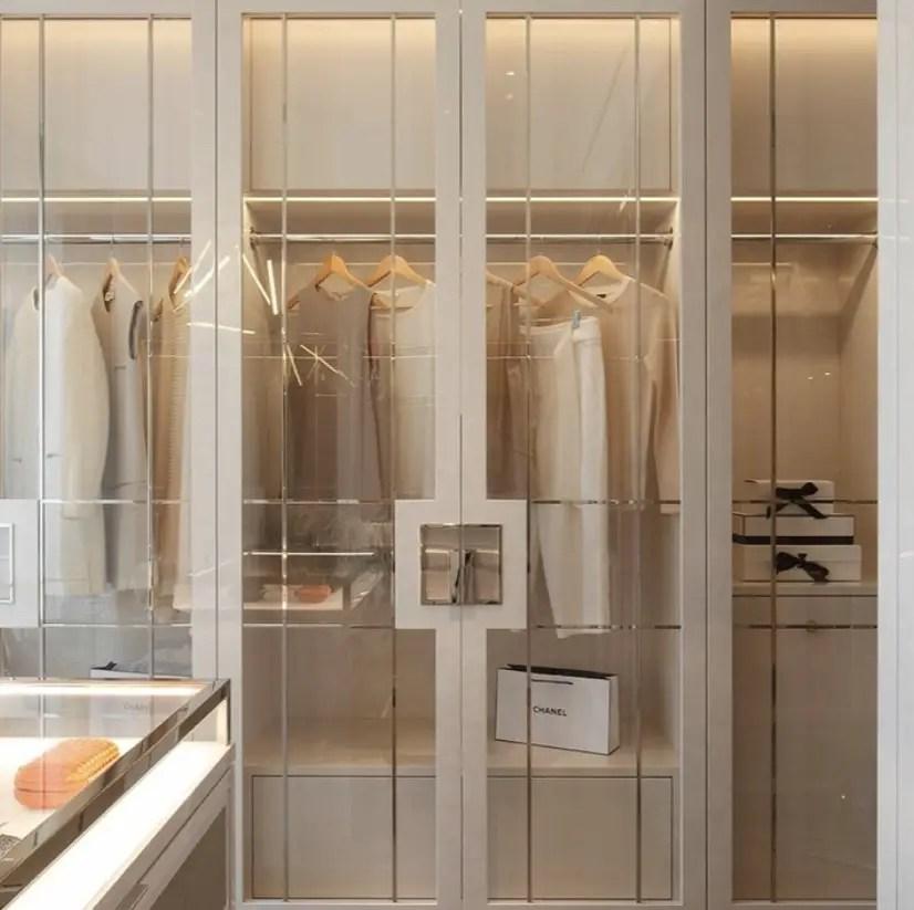Le rangement des vêtements en blanc et les portes en verre.