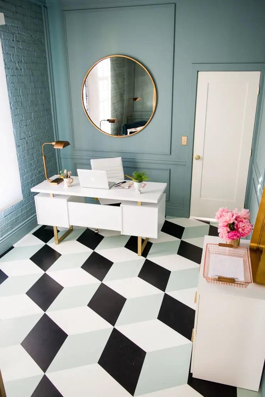 Ce sol repeint en noir, blanc, et bleu menthe en motif cubique donne de la personnalité à un bureau minimalist. L'exemple parfait pour comment cette tendance déco 2020 peut ajouter votre personnalité à une pièce.