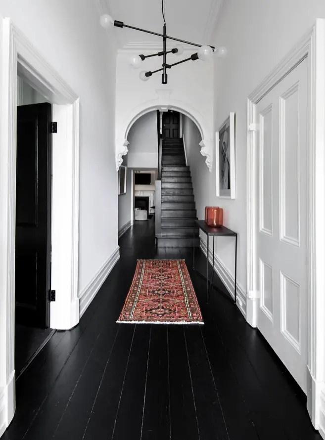 Ce parquet peint en noir, un joli exemple de cette tendance déco 2020, est une belle contraste contre les murs blancs.