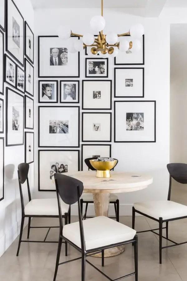 Salle à manger en noir et blanc avec un mur galerie.