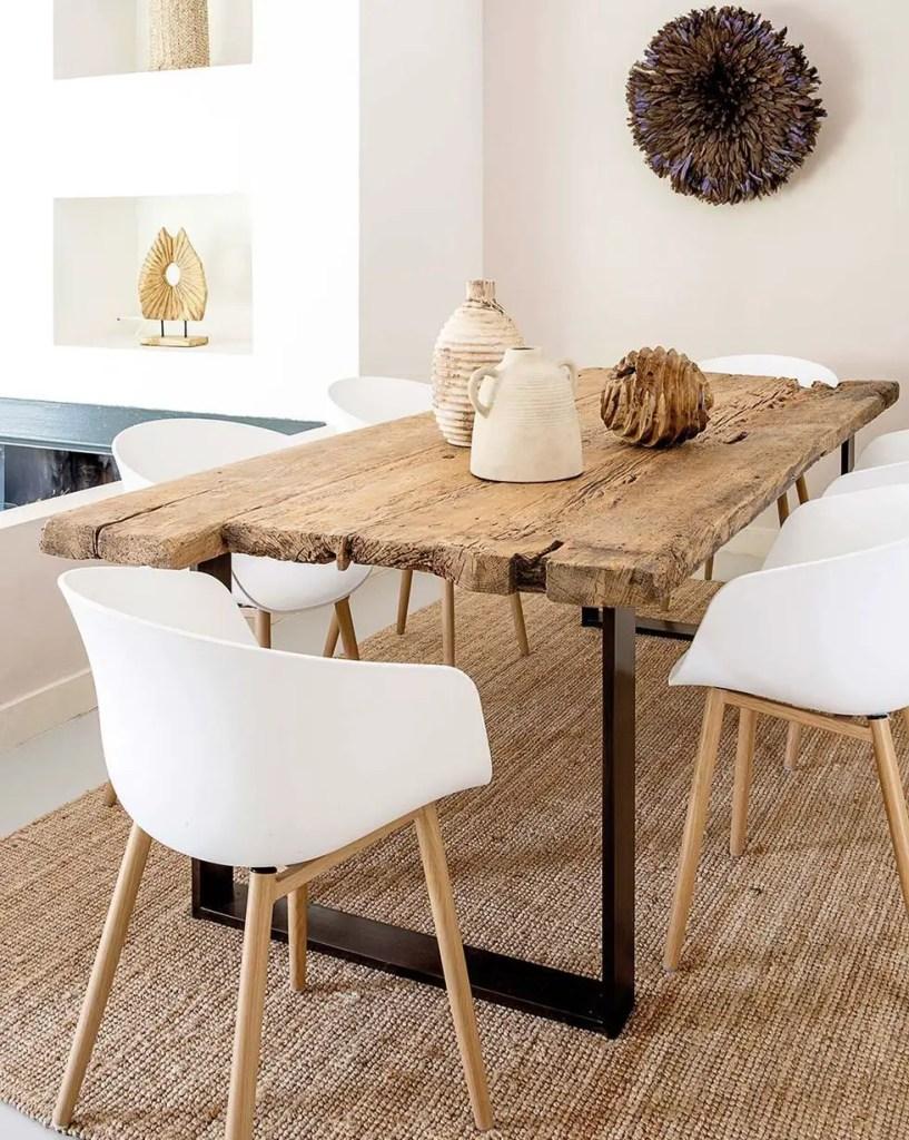 table rustique à bords irréguliers avec chaises blanches et modernes