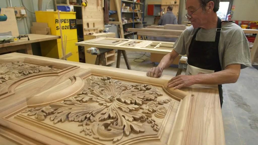 artisan au travail sur une porte en bois sculpté