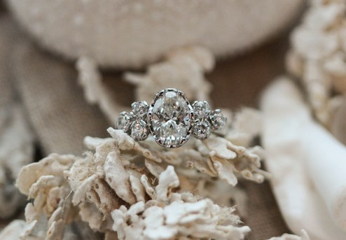 Platinum crown setting with oval center stone and round brilliant diamond cluster.
