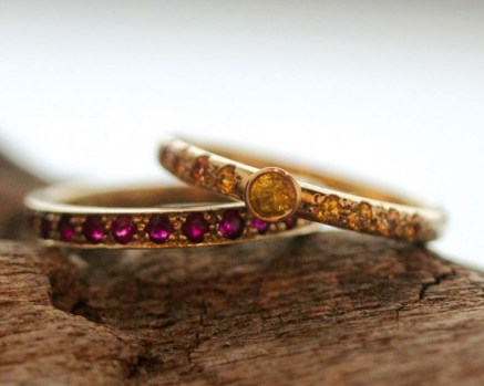 Warm tones from these paved and bezel set sapphires beautifully compliment the deep red ruby band