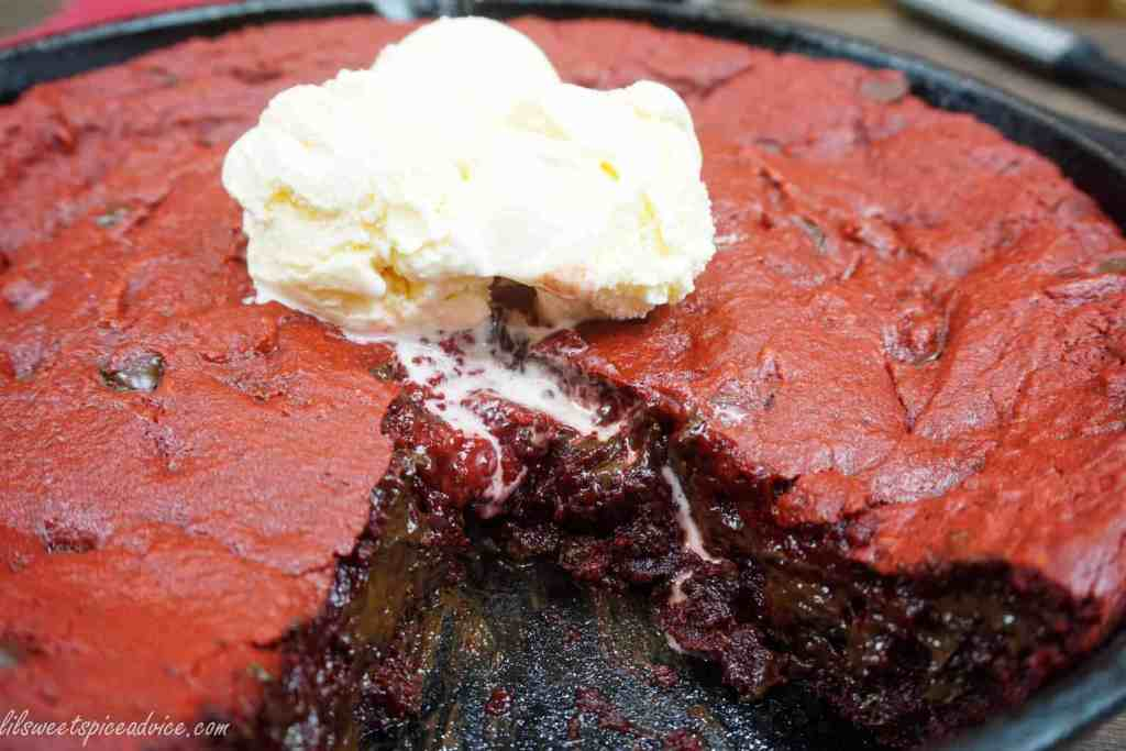 Red Velvet Ooey Gooey Butter Skillet Cookie -- The search for the perfect skillet cookie is officially over! With all of the flavor of a red velvet cake and the gooey butter cake factor this skillet cookie is sure to please the crowd. -- lilsweetspiceadvice.com #skilletcookie #redvelvet #gooeybutter